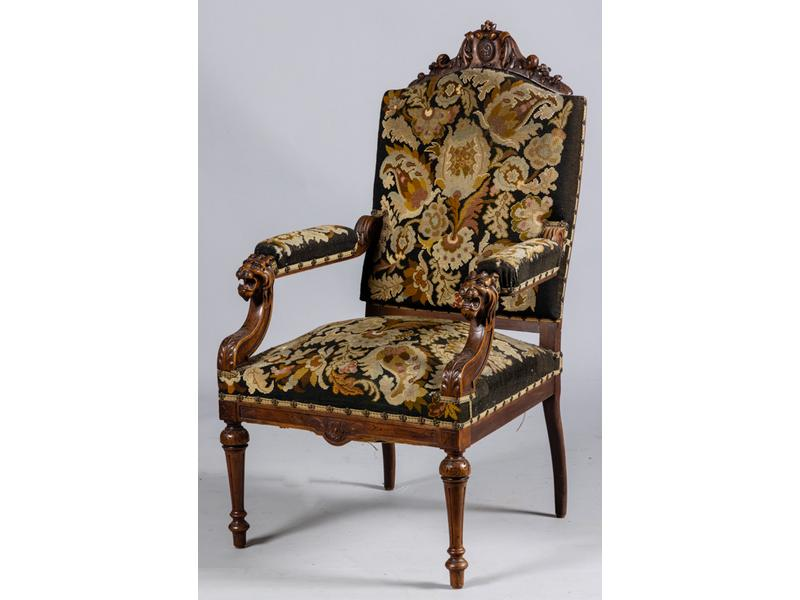 Fauteuil de cabinet de style Henri II en bois naturel mouluré et richement sculpté.  Dossier à décor d'un cartouche chiffré, supports d'accotoirs à mufles de lion.  Garniture au point de croix.